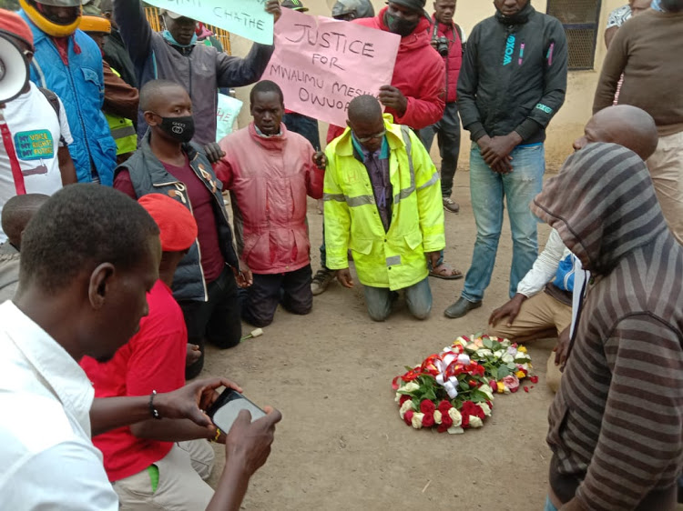 Protesters pray at the scene of accident where three locals were knocked to death by a car belonging to Kibos Sugar Company boss