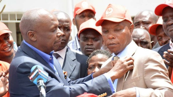 CAPTION: KANU chairman Gideon Moi and Laikipia Senator aspirant Maina Njenga hold the Kanu flag during a press conference at the party's headquarters after the latter's defection from Jubilee, March 22, 2017